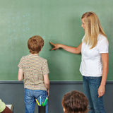 Δάσκαλος που βοηθά το παιδί στον πίνακα κιμωλίας Στοκ εικόνα με δικαίωμα ελεύθερης χρήσης