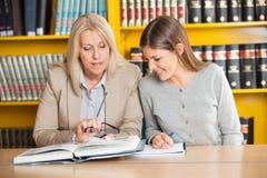 Δάσκαλος που εξηγεί στο σπουδαστή στη βιβλιοθήκη κολλεγίου Στοκ φωτογραφίες με δικαίωμα ελεύθερης χρήσης