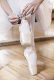 Δένοντας παντόφλες χορευτών μπαλέτου γύρω από τον αστράγαλό της Στοκ φωτογραφία με δικαίωμα ελεύθερης χρήσης