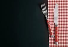 Δίκρανο και μαχαίρι στο ελεγχμένο επιτραπέζιο ύφασμα Στοκ Εικόνες