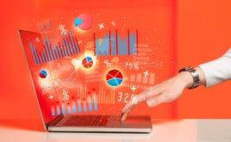Δακτυλογράφηση χεριών στο σύγχρονο φορητό υπολογιστή lap-top με τα εικονίδια γραφικών παραστάσεων Στοκ εικόνα με δικαίωμα ελεύθερης χρήσης