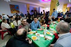 Διαφορετικοί άνθρωποι που μιλούν στους πίνακες στο γεύμα φιλανθρωπίας Χριστουγέννων για τους αστέγους Στοκ Εικόνα