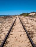 Διαδρομές σιδηροδρόμου χάλυβα στην παραλία άμμου Στοκ Εικόνες
