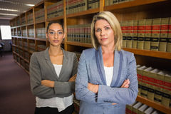 Δικηγόροι που εξετάζουν τη κάμερα στη βιβλιοθήκη νόμου Στοκ εικόνα με δικαίωμα ελεύθερης χρήσης