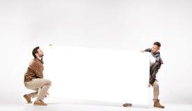 Δύο έξυπνοι τύποι που φέρνουν το βαρύ πίνακα διαφημίσεων Στοκ εικόνες με δικαίωμα ελεύθερης χρήσης