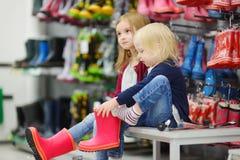 Δύο αδελφές που επιλέγουν και που προσπαθούν στις νέες μπότες βροχής Στοκ Φωτογραφία