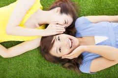 Δύο αδελφές που ψιθυρίζουν το κουτσομπολιό στη χλόη Στοκ εικόνα με δικαίωμα ελεύθερης χρήσης