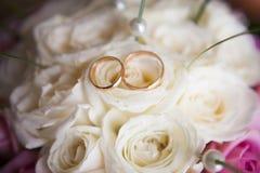 Δύο γαμήλια δαχτυλίδια στην κινηματογράφηση σε πρώτο πλάνο λουλουδιών Στοκ Εικόνες