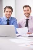 Δύο επιχειρησιακά άτομα που εργάζονται μαζί στο lap-top στην αρχή Στοκ Εικόνα