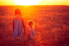 Δύο κορίτσια παιδιών στον τομέα ηλιοβασιλέματος Στοκ Εικόνες
