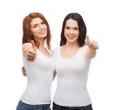 Δύο κορίτσια στην άσπρη παρουσίαση μπλουζών φυλλομετρούν επάνω Στοκ φωτογραφία με δικαίωμα ελεύθερης χρήσης
