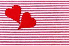 Δύο κόκκινες καρδιές σε ένα ριγωτό υπόβαθρο Στοκ εικόνες με δικαίωμα ελεύθερης χρήσης