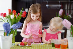 Δύο μικρές αδελφές που χρωματίζουν τα αυγά Πάσχας Στοκ εικόνες με δικαίωμα ελεύθερης χρήσης