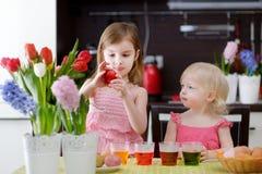 Δύο μικρές αδελφές που χρωματίζουν τα αυγά Πάσχας Στοκ εικόνα με δικαίωμα ελεύθερης χρήσης