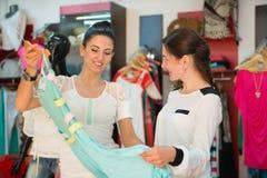 Δύο νέα κορίτσια στη μπουτίκ που επιλέγουν το φόρεμα Στοκ εικόνες με δικαίωμα ελεύθερης χρήσης