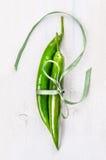Δύο πράσινα πιπέρια τσίλι που δένονται με την κορδέλλα Στοκ Φωτογραφίες