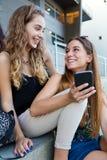 Δύο σπουδαστές που έχουν τη διασκέδαση με τα smartphones μετά από την κατηγορία Στοκ φωτογραφία με δικαίωμα ελεύθερης χρήσης