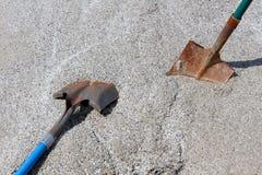 Δύο φτυάρια εργασίας στο ανάχωμα του αμμοχάλικου. Στοκ Εικόνες