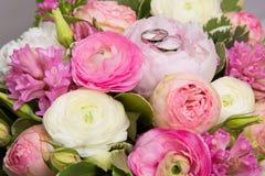 Γαμήλια δαχτυλίδια στην ανθοδέσμη των άσπρων και ρόδινων peonies Στοκ Εικόνες