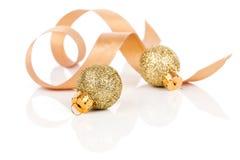 Δύο χρυσές σφαίρες διακοσμήσεων Χριστουγέννων με την κορδέλλα σατέν Στοκ Εικόνες