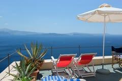 Δύο deckchairs στη στέγη santorini νησιών λόφων της Ελλάδας κτηρίων Στοκ εικόνα με δικαίωμα ελεύθερης χρήσης