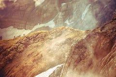Δύσκολα βουνά με το χιόνι παγετώνων και τη σκιαγραφία οδοιπόρων πέρα Στοκ φωτογραφία με δικαίωμα ελεύθερης χρήσης