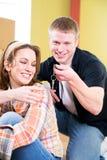 Двигать: Человек принимает ключ на ключевой цепи от женщины Стоковые Фото
