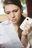 Девочка-подросток изучая мобильный телефон Билл смотря потревоженный Стоковые Фотографии RF