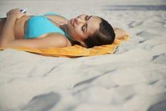 Девочка-подросток используя mp3 плэйер лежа на пляжном полотенце Стоковые Фото