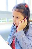 Девушка Азии используя телефон Стоковые Изображения