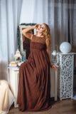 Девушка в коричневом макси платье Стоковые Фото