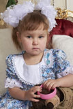 Девушка в платье хлопка была белым воротником и большая белизна обхватывает держать розовый браслет и смотреть телезрителя Стоковые Фотографии RF