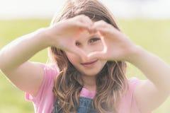 Девушка делая знак сердца влюбленности Стоковые Фотографии RF