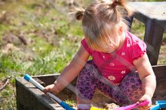 Девушка играя в коробке песка Стоковые Изображения