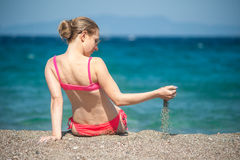 Девушка играя с песком на пляже Стоковая Фотография RF