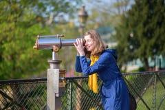 Девушка используя телескоп для sightseeing в Париже Стоковая Фотография
