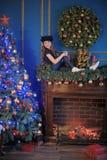 Девушка около рождества украсила дерево Стоковые Фотографии RF