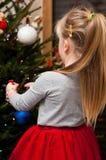 Девушка одевая рождественскую елку Стоковое Изображение