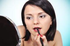 Девушка прикладывая губную помаду на губах Стоковое Фото