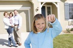 Девушка при семья держа новый домашний ключ Стоковое Фото
