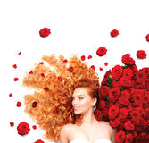 Девушка с курчавыми красными волосами и красивыми красными розами Стоковая Фотография