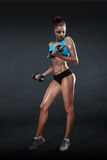 Девушка фитнеса с гантелями на темной предпосылке Стоковые Фотографии RF