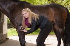 Девушка чистит ее пони щеткой Стоковая Фотография RF