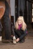 Девушка чистит ее пони щеткой Стоковое фото RF