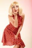 Девушка Pinup в платье белокурого парика ретро дуя поцелуй Стоковая Фотография RF