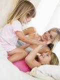 девушки кровати играя 2 детенышей женщины Стоковое Изображение