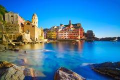 Деревня, церковь, утесы и море Vernazza затаивают на заходе солнца. Cinque Стоковые Фото
