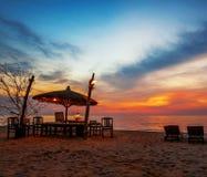 Деревянные стулья и зонтики на пляже песка Стоковое Изображение RF