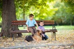 Дети в парке с немецкой овчаркой Стоковые Фотографии RF