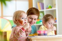 Дети играя и крася Стоковые Изображения